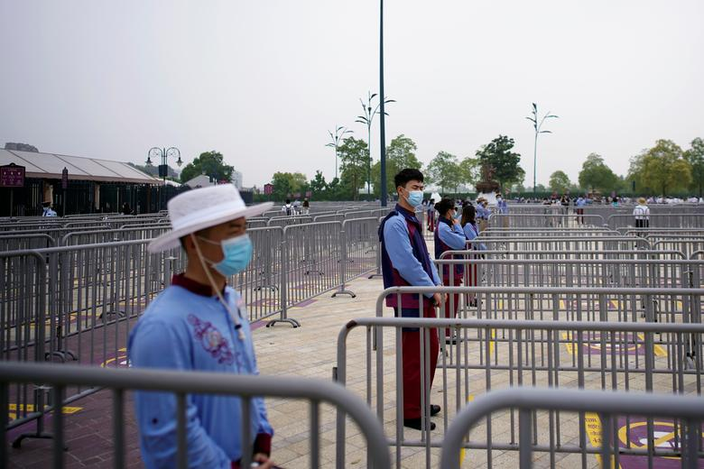 Співробітники, що носять маски, стоять біля тематичного парку Shanghai Disneyland, коли він знову відкривається. REUTERS / Aly Song