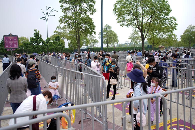 Відвідувачі в масках шикуються в чергу, щоб увійти. REUTERS / Aly Song
