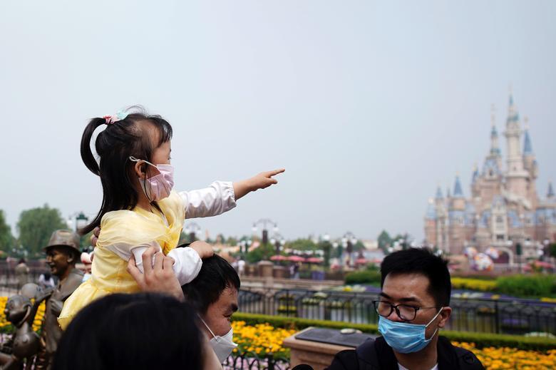 Відвідувачі в лицьових масках в Шанхайському Діснейлендском тематичному парку в міру його відкриття. REUTERS / Aly Song