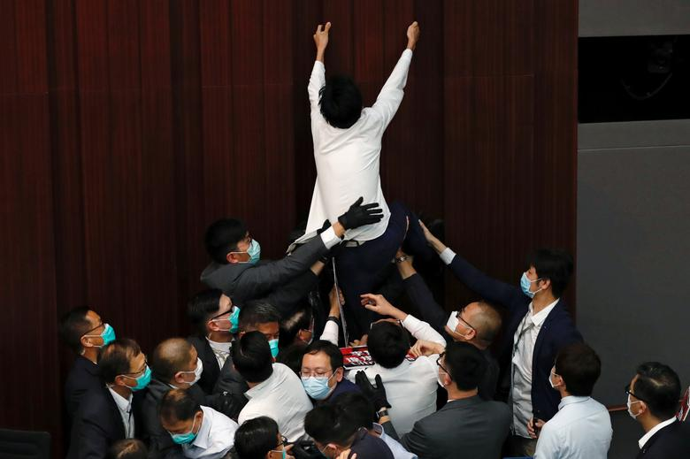 Pan-democratic legislator Eddie Chu Hoi-dick scuffles with security and pro-China legislators during the Legislative Council's House Committee meeting in Hong Kong, China May 8, 2020. Rival lawmakers scuffled in legislature in a row over electing the chairman of a key committee, a fresh sign of rising political tension as the coronavirus pandemic eases in the Chinese-ruled city. REUTERS/Tyrone Siu
