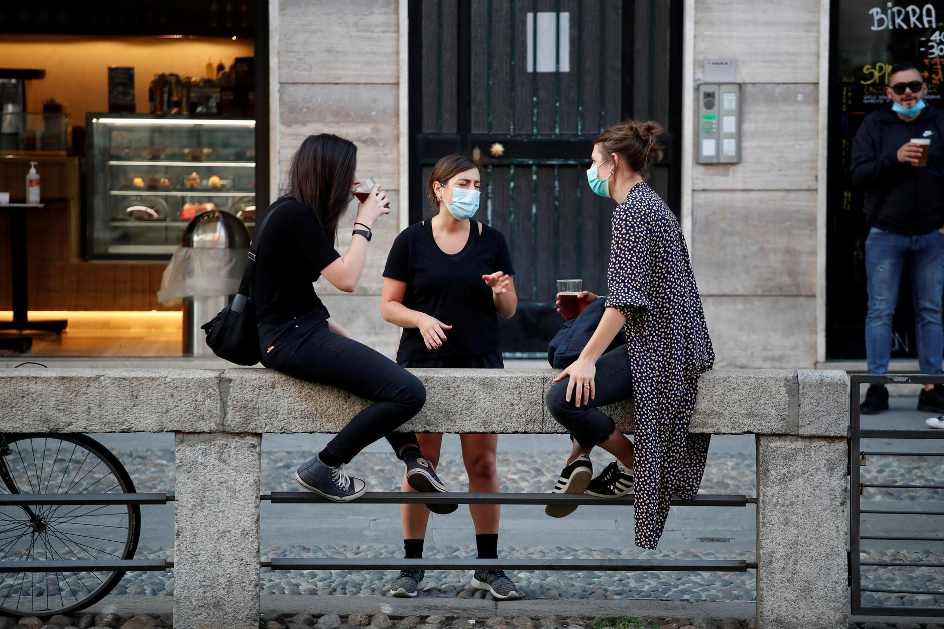 People enjoy a drink in the Navigli area, as Italy eases some of the lockdown measures put in place during the coronavirus disease (COVID-19) outbreak, in Milan, Italy May 18, 2020. REUTERS/Alessandro Garofalo