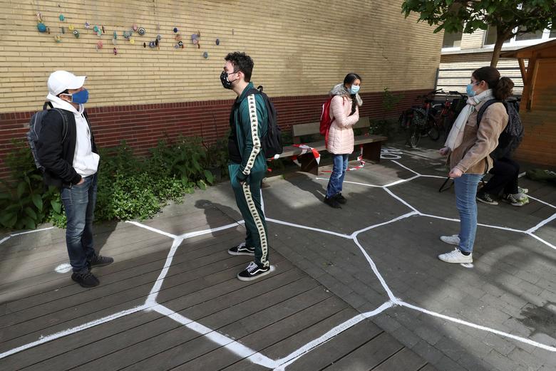 Учащиеся в защитных масках разговаривают, практикуя социальное дистанцирование во дворе средней школы во время ее открытия в Брюсселе, Бельгия, 15 мая. REUTERS / Yves Herman & nbsp;