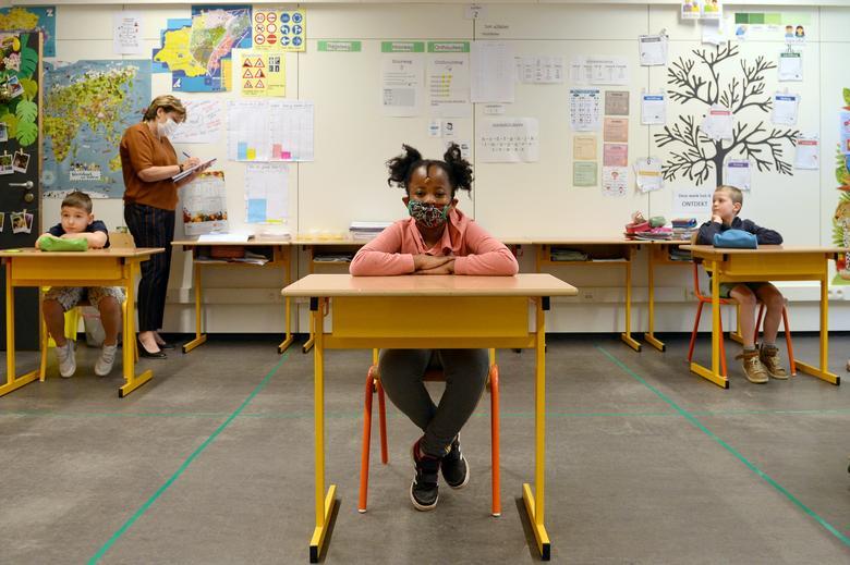 Школьник и учитель носят маски в классе в начальной школе во время ее открытия в Брюсселе, Бельгия, 15 мая. РЕЙТЕР / Йоханна Герон