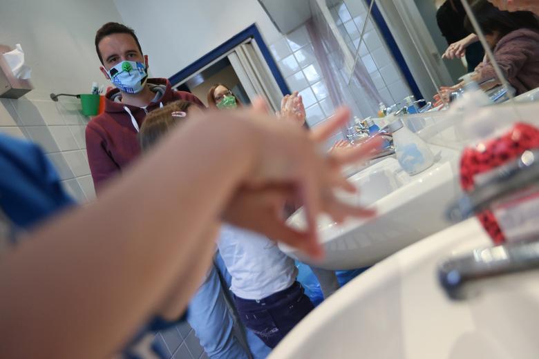 Учитель учит детей дошкольного возраста правильно мыть руки в первый день после открытия в Берлине, Германия, 14 мая. РЕЙТЕР / Фабрицио Бенш