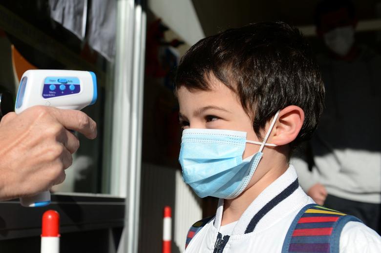Учитель измеряет температуру детей на входе в начальную школу во время ее открытия в Брюсселе, Бельгия, 15 мая. РЕЙТЕР / Йоханна Герон
