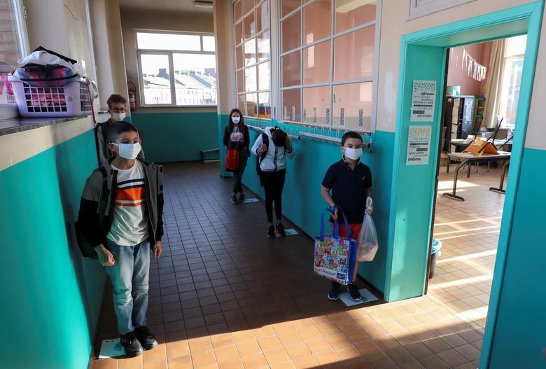 Учащиеся стоят на отметках социального дистанцирования перед входом в класс в начальной школе во время ее открытия в Хьюмете, Бельгия, 18 мая. РЕЙТЕР / Ив Герман