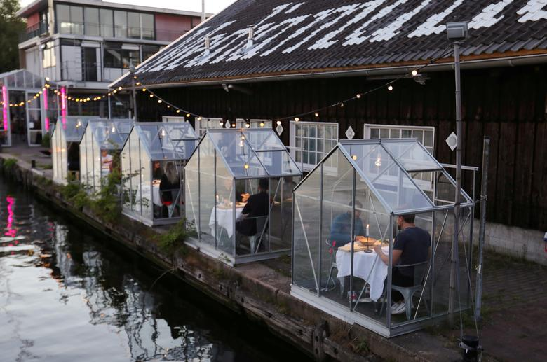 A restaurant tests servers providing drinks and food to models pretending to be guests in safe 'quarantine greenhouses' in which clients can dine in Amsterdam, May 5. REUTERS/Eva Plevier