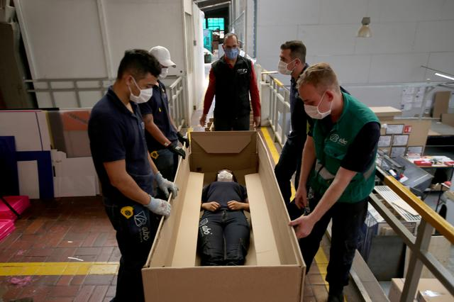 Employees of the company ''ABC Display'' demonstrate how a hospital bed that they manufacture is transformed into a cardboard coffin, amid the coronavirus disease (COVID-19) outbreak in Bogota, Colombia May 21, 2020.  REUTERS/Luisa Gonzalez