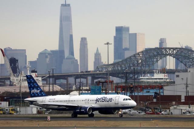 FILE PHOTO: A JetBlue passenger jet lands with New York City as a backdrop, at Newark Liberty International Airport, New Jersey, U.S. December 6, 2019. REUTERS/Chris Helgren/File Photo