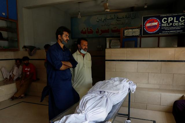 Family members stand beside a body of a relative, who was killed in a plane crash, in Karachi, Pakistan May 23, 2020. REUTERS/Akhtar Soomro