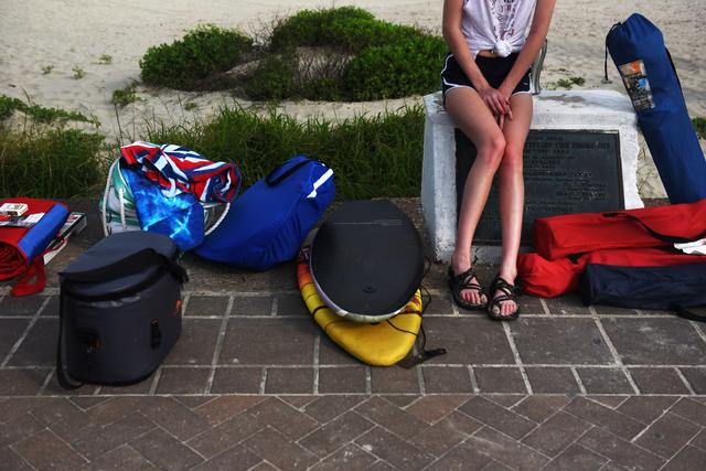 A woman sits with her family's beach gear after coronavirus disease (COVID-19) restrictions were lifted at the beginning of May, in time at the start of the Memorial Day weekend in Galveston, Texas, U.S. May 22, 2020. REUTERS/Callaghan O'Hare