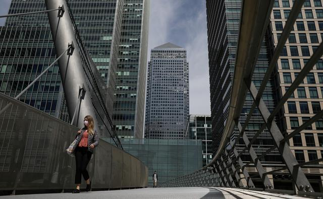 FILE PHOTO: A woman wearing a face mask crosses a bridge in front of One Canada Square in Canary Wharf, following the outbreak of the coronavirus disease (COVID-19), London, Britain, May 18, 2020. REUTERS/Simon Dawson/File Photo