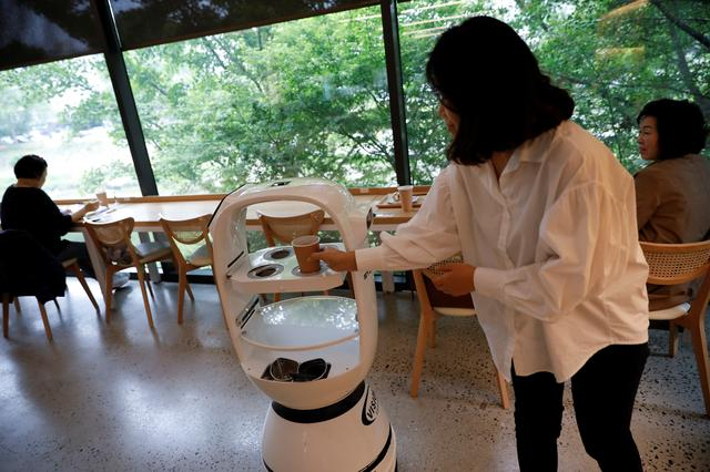 A customer picks up her drink at a cafe where a robot that takes orders, makes coffee and brings the drinks straight to customers is being used in Daejeon, South Korea, May 25, 2020. REUTERS/Kim Hong-Ji