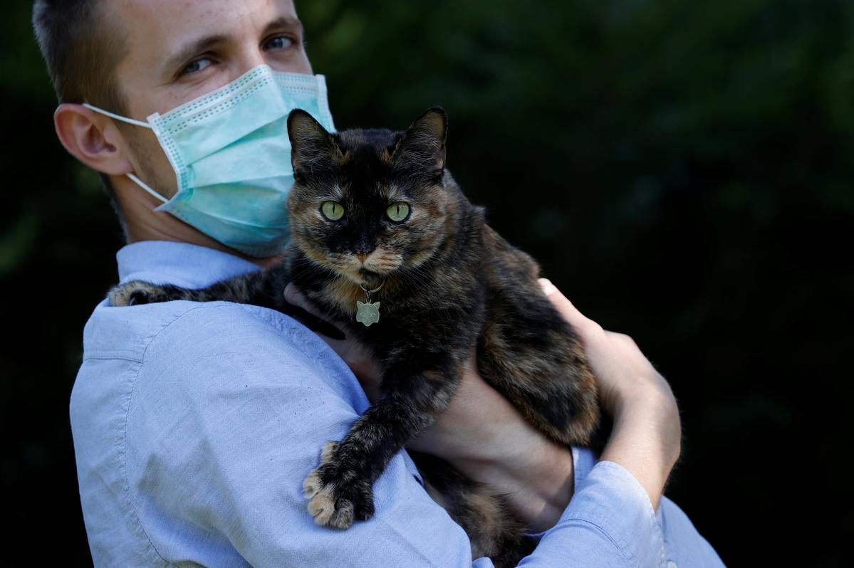Brian, 24 year-old, suspected to have been infected by the SARS-CoV-2 poses in his garden with Papille, his 9 year-old cat who recovered after being tested positive for the virus amid the coronavirus disease (COVID-19) outbreak, in Athis-Mons, near Paris, France, May 27, 2020. Picture taken May 27, 2020. REUTERS/Christian Hartmann