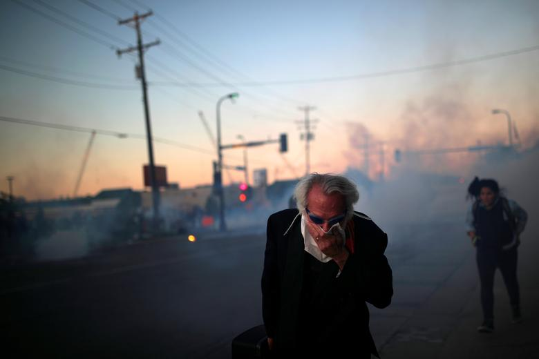 30 Mayıs 2020, Minneapolis'te gösteriler devam ederken bir adam yüzünü örter. REUTERS / Carlos Barria