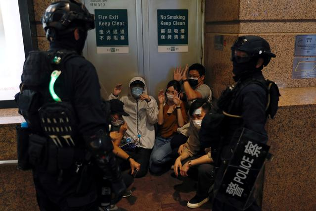 People are detained by riot police during a march against a new national security law on the anniversary of Hong Kong\u0027s handover to China from Britain in Hong Kong, China July 1, 2020. Police fired water cannon and tear gas and arrested more than 300 people as demonstrators defied the sweeping security legislation introduced by China to snuff out dissent in the former British colony. REUTERS/Tyrone Siu