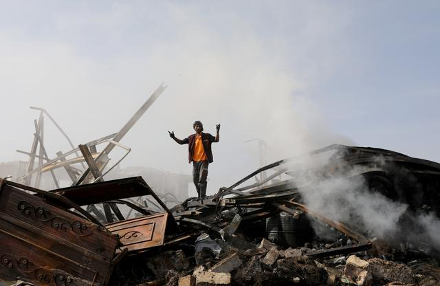 A worker stands on the wreckage of a vehicle oil and tires store hit by Saudi-led air strikes in Sanaa, Yemen July 2, 2020. REUTERS/Khaled Abdullah