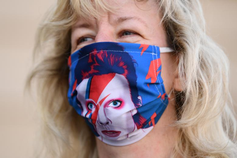 A woman wearing a face mask depicting a picture of David Bowie takes part in event industry staff protest against coronavirus measures, in Berlin, Germany, July 24, <span dir=