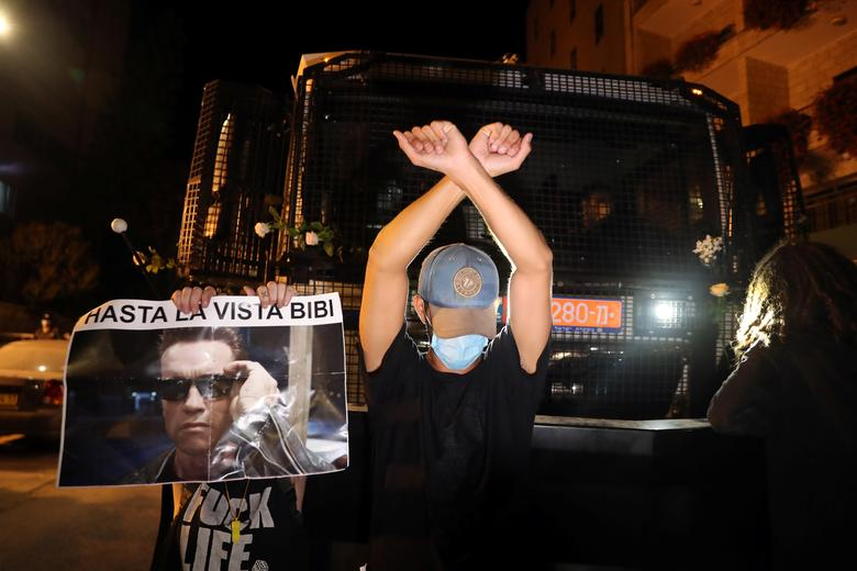 A man stands in front of a police truck during a protest against Prime Minister Benjamin Netanyahu and his government's handling of the coronavirus crisis, near Netanyahu's residence in Jerusalem July 24, <span dir=
