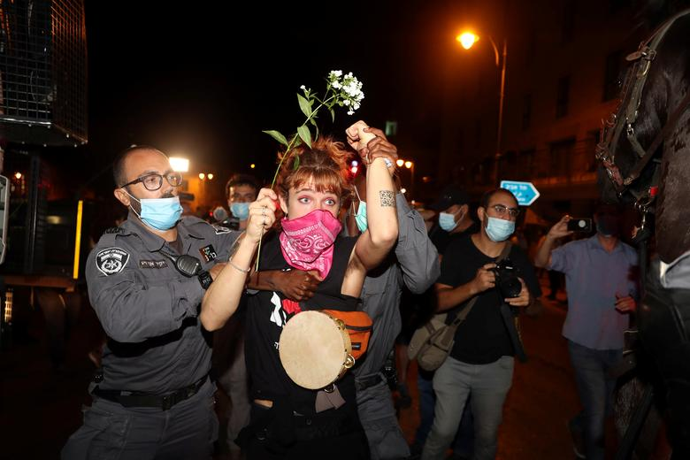 Police detain a woman during a protest against Prime Minister Benjamin Netanyahu and his government's handling of the coronavirus crisis, near Netanyahu's residence in Jerusalem July 23, <span dir=