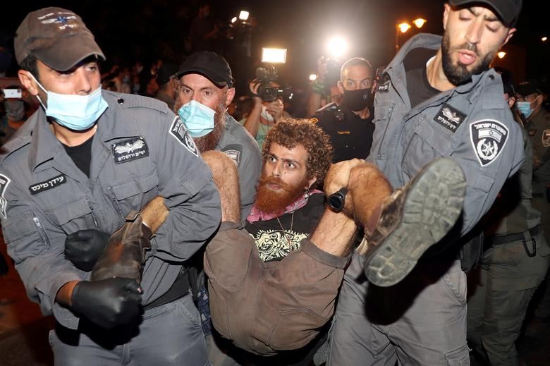 Police detain a man during a protest against Prime Minister Benjamin Netanyahu and his government's handling of the coronavirus crisis, near Netanyahu's residence in Jerusalem July 23, <span dir=