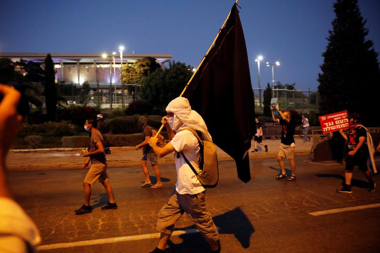 Israelis march as they protest against Israeli Prime Minister Benjamin Netanyahu and his government's response to the financial fallout of the coronavirus crisis, outside the Knesset, Israeli parliament in Jerusalem July 21, <span dir=