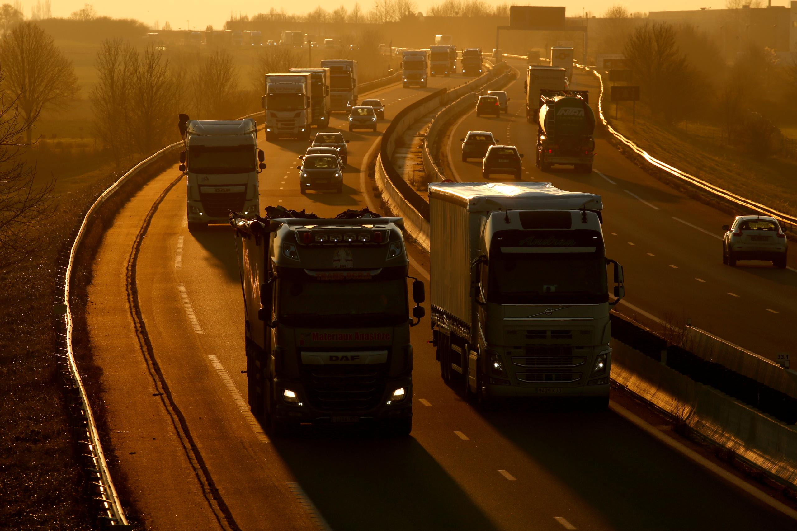 FILE PHOTO: Trucks and cars drive on the Paris-Bruxelles highway during sunset in Tilloy-lez-Cambrai, France, December 4, 2019. REUTERS/Pascal Rossignol/File Photo