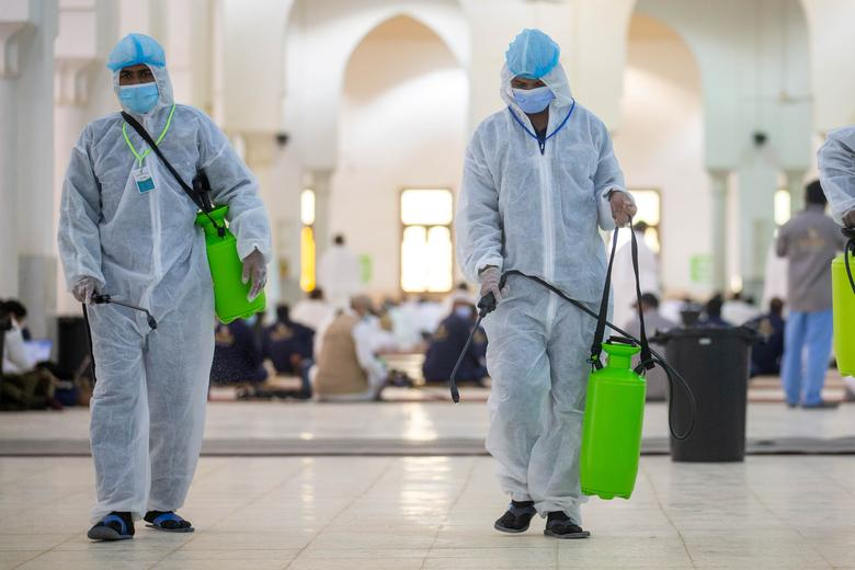 Health workers wearing personal protective equipment (PPE) disinfect the floor as Muslim pilgrims pray inside Namira Mosque in Arafat to mark Haj's most important day, Day of Arafat, July 30, <span dir=