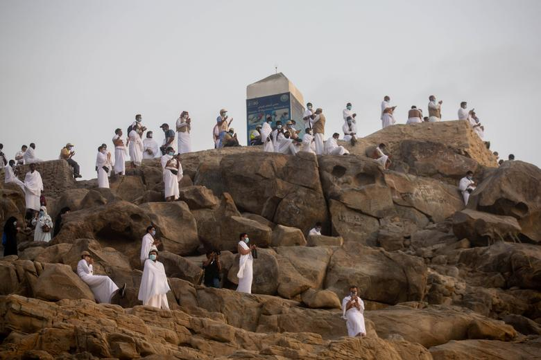 Muslim pilgrims wear protective face masks, as they pray on Mount Mercy on the plains of Arafat during the annual Haj pilgrimage, July 30, <span dir=