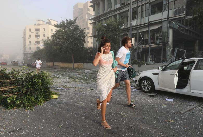 La gente se refugia tras una explosión en la zona portuaria de Beirut, Líbano, 4 de agosto de 2020. REUTERS / Mohamed Azakir