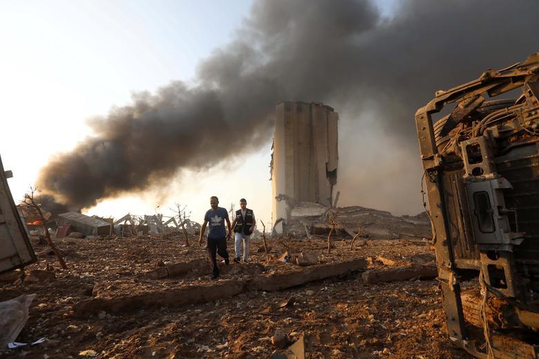 Hombres caminan en el lugar de una explosión en Beirut, Líbano, 4 de agosto de 2020. REUTERS / Mohamed Azakir