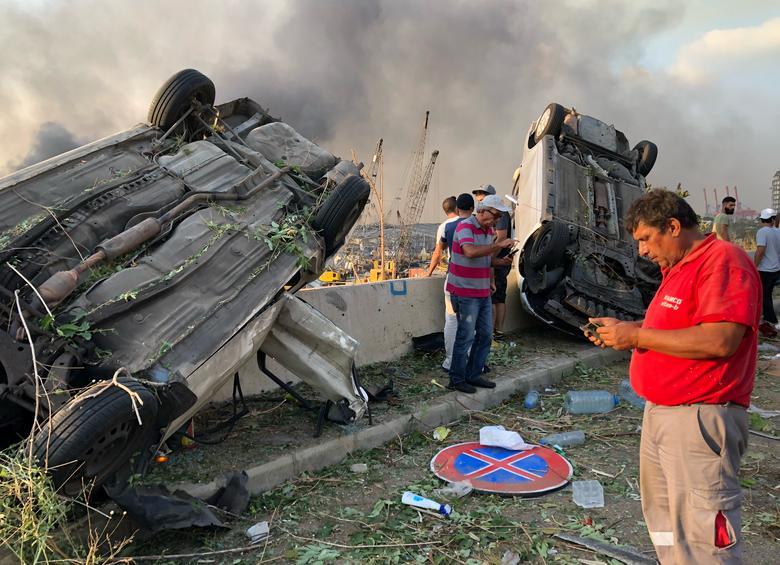 Las personas se paran cerca de automóviles dañados después de una explosión en Beirut, Líbano, 4 de agosto de 2020. REUTERS / Issam Abdallah