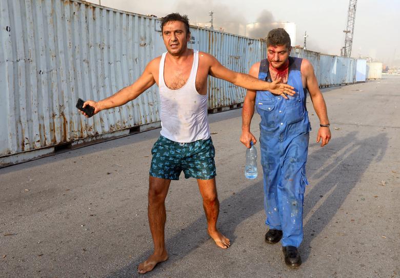 Yaralı erkekler 4 Ağustos 2020, Lübnan Beyrut'ta meydana gelen bir patlamadan sonra görülüyor. REUTERS / Mohamed Azakir
