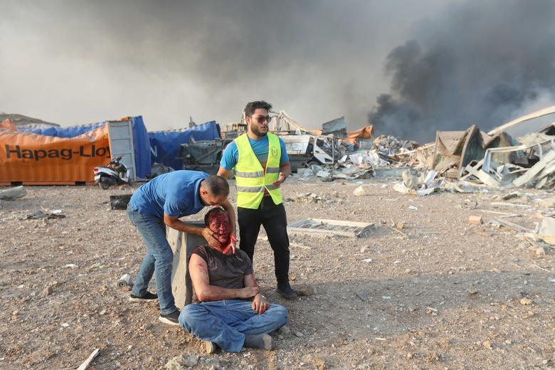 4 Ağustos 2020'de Beyrut, Lübnan'da meydana gelen patlamada yaralı bir adama yardım edildi. REUTERS / Mohamed Azakir