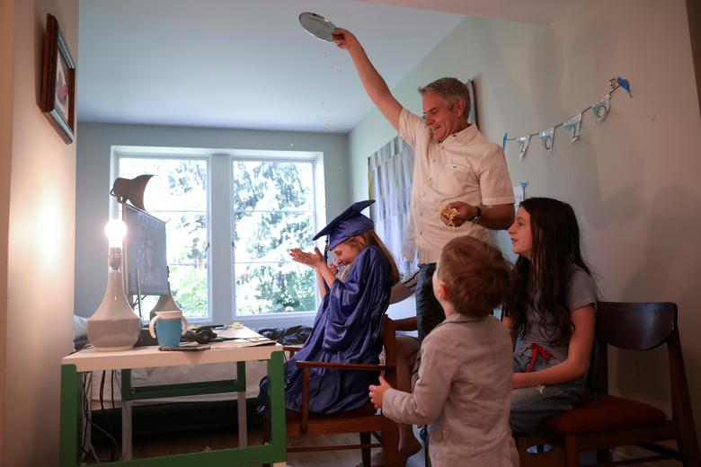 Doug Hassebroek pours confetti over his daughter Lydia, celebrating her graduation ceremony at their home in Brooklyn, New York, June 17, 2020. REUTERS/Caitlin Ochs