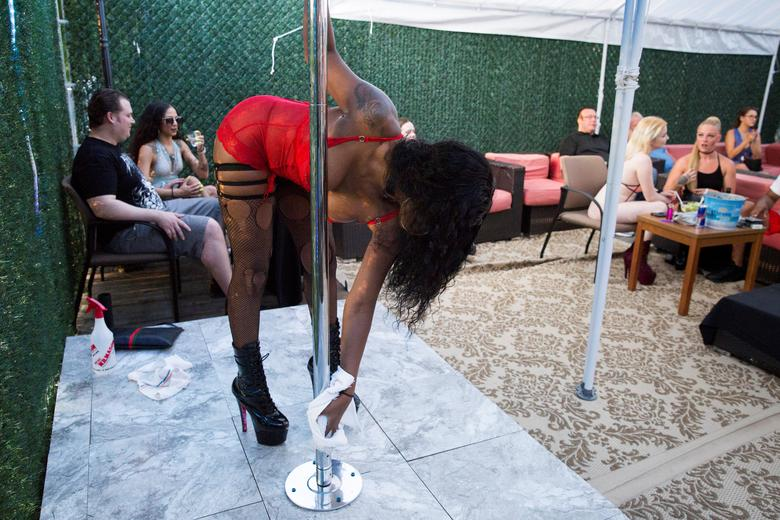 A dancer sanitizes the pole before performing on the outside patio at Cheerleaders Gentlemen's Club in Gloucester City, New Jersey, July 17, 2020. Cheerleaders received a Paycheck Protection Program (PPP) loan from the Small Business Administration. REUTERS/Rachel Wisniewski