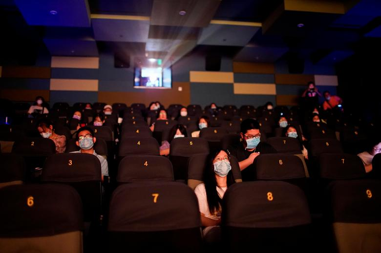 People wearing face masks watch a movie in a cinema as it reopens in Shanghai, China July 20, 2020. REUTERS/Aly Song