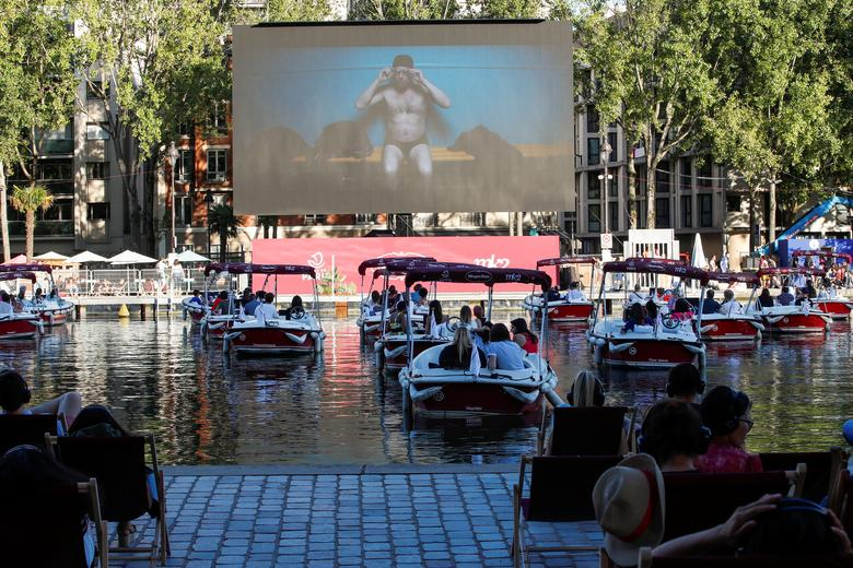 """People watch the film """"Le Grand Bain"""" seat on beach chairs and from boats at the Cinema on the water (cinema sur l'eau) as a floating cinema with 38 socially distant electric boats kicks off the Paris Plages summer event along the Bassin de la Villette, in Paris, France July 18, 2020. REUTERS/Gonzalo Fuentes"""