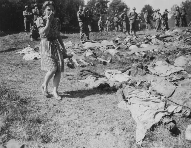 A German resident is overcome as she walks past the exhumed bodies of some of 800 slave workers murdered by SS guards near Namering, Germany, May 17, 1945. U.S. National Archives/via REUTERS