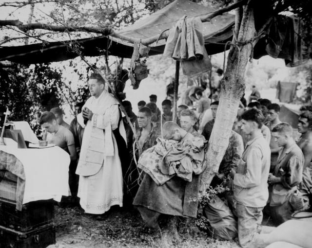 With a canvas tarpaulin for a church and packing cases for an altar, a Navy chaplain holds mass for Marines at Saipan, June 1944. U.S. National Archives/via REUTERS