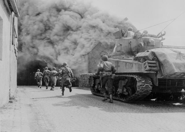 U.S. soldiers of the 55th Armored Infantry Battalion and tank of the 22nd Tank Battalion move through a smoke filled street in Wernberg, Germany, April 22, 1945. U.S. National Archives/via REUTERS