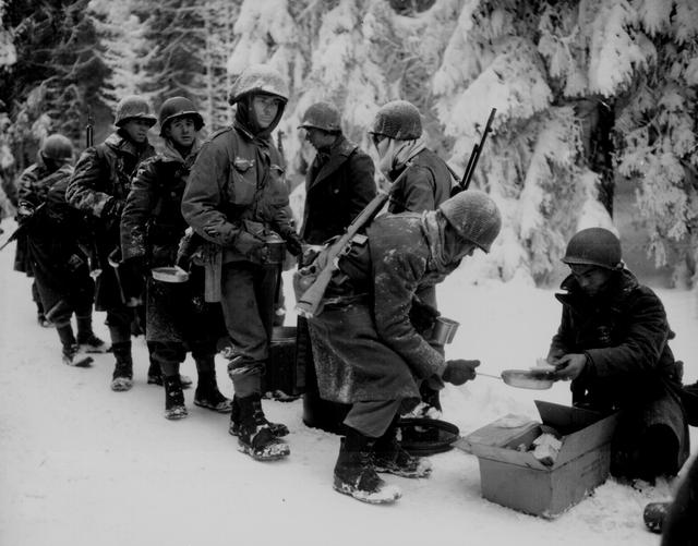 U.S. soldiers of the 347th Infantry Regiment are served food on their way to La Roche, Belgium, January 13, 1945. U.S. National Archives/via REUTERS