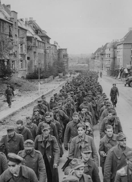 A procession of German prisoners captured by U.S. soldiers during the taking of Aachen march through the streets of the ruined city, in Aachen, Germany, October 1944. U.S. National Archives/via REUTERS