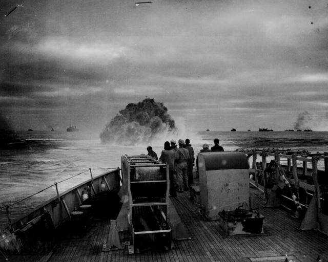Coast Guardsmen on the deck of the U.S. Coast Guard Cutter Spencer watch the explosion of a depth charge while providing convoy protection from Nazi U-boats, April 17, 1943. U.S. National Archives/via REUTERS
