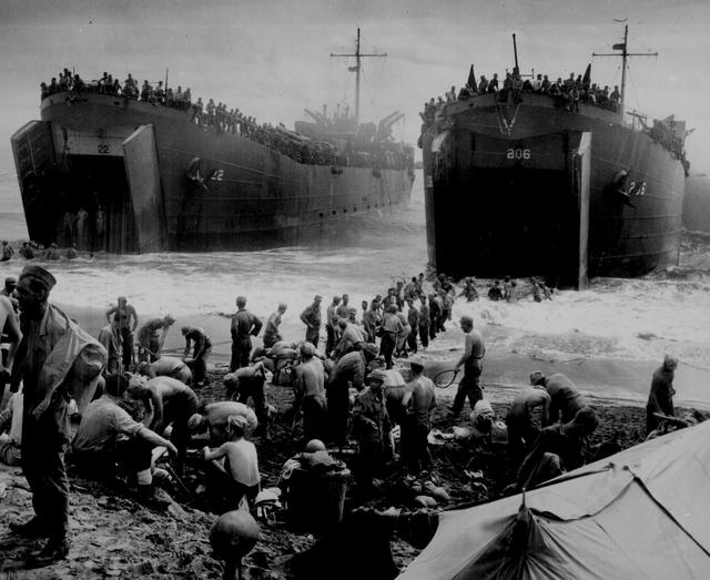 Two U.S. Coast Guard-manned LST\u0027s open their great jaws in the surf on Leyte Island beach as soldiers strip down and build sandbag piers out to the ramps to speed up unloading operations, Leyte, Philippines, 1944. U.S. National Archives/via REUTERS