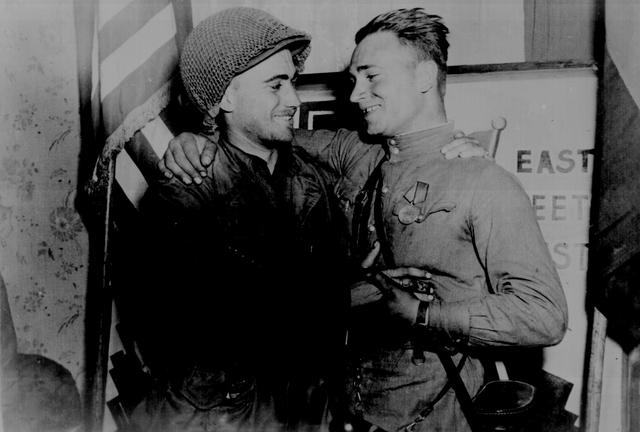 U.S. 2nd Lt. William Robertson and Soviet Lt. Alexander Sylvashko in front of a sign symbolizing the historic meeting of the Russian and American Armies, near Torgau, Germany, April 25, 1945. U.S. National Archives/via REUTERS