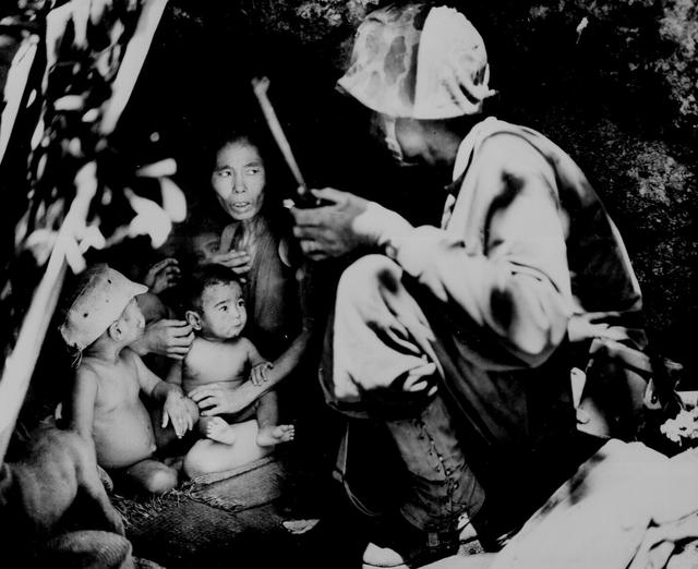 A member of a U.S. Marine patrol on Saipan finds a Japanese family hiding in a hillside cave during fighting on Saipan, June 21, 1944. The mother, four children and a dog were in the cave. U.S. National Archives/via REUTERS