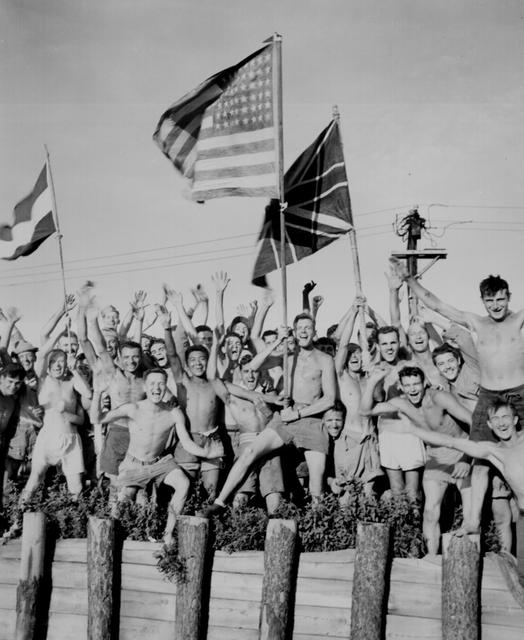 Gaunt allied prisoners of war cheer rescuers from the U.S. Navy at Aomori camp near Yokohama, Japan, August 29, 1945. The prisoners are waving flags of the United States, Great Britain and Holland. U.S. National Archives/via REUTERS