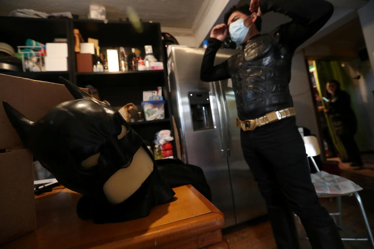 FILE PHOTO: A Chilean trader and so-called 'Batman solidario' (Solidarity Batman) prepares to put on his mask as he dresses up before cooking at his house, during the global outbreak of the coronavirus disease (COVID-19), in Santiago, Chile August 13, 2020. REUTERS/Ivan Alvarado