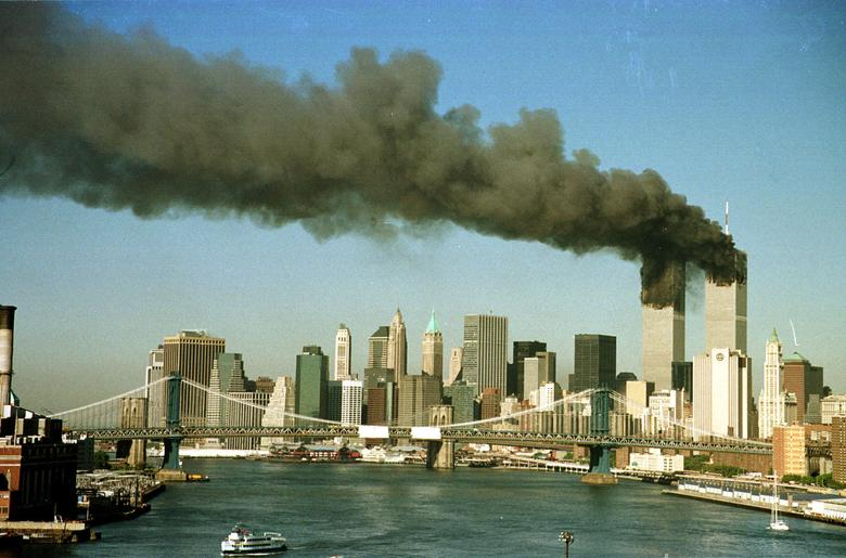 The towers of the World Trade Center pour smoke shortly after being struck by hijacked commercial aircraft, September 11, 2001. REUTERS/Brad Rickerby